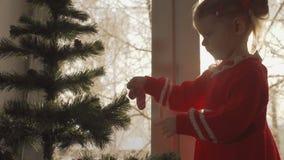 Il vestito dalla bambina in rosso che decora l'albero di Natale con un pan di zenzero stock footage