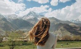 Il vestito dalla ragazza dietro l'estate guarda i picchi della neve delle montagne fotografie stock