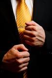 Il vestito dell'uomo con il primo piano giallo delle mani e del legame Immagini Stock