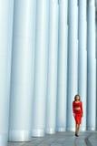 Il vestito della ragazza in rosso ottiene le colonne alte Immagine Stock
