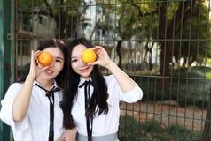 Il vestito grazioso cinese asiatico adorabile dello studente di usura di due ragazze nei migliori amici della scuola sorride frut Fotografia Stock Libera da Diritti