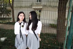 Il vestito grazioso cinese asiatico adorabile dello studente di usura di due ragazze nei migliori amici della scuola sorride gioc Fotografia Stock