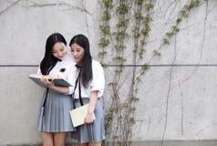 Il vestito grazioso cinese asiatico adorabile dello studente di usura di due ragazze nei migliori amici della scuola sorride libr Immagini Stock Libere da Diritti