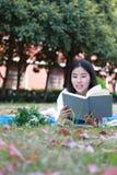 Il vestito grazioso cinese asiatico adorabile sveglio dello studente di usura della ragazza a scuola che si trova sul libro di le Fotografia Stock Libera da Diritti