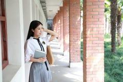 Il vestito grazioso cinese asiatico adorabile sveglio dello studente di usura della ragazza a scuola nella classe gode del sorris Fotografia Stock