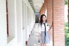 Il vestito grazioso cinese asiatico felice dello studente di usura della ragazza a scuola fa una pausa una parete in natura in pr Fotografia Stock
