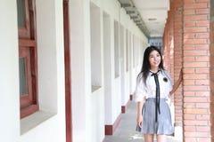 Il vestito grazioso cinese asiatico felice dello studente di usura della ragazza a scuola fa una pausa una parete in natura in pr Fotografie Stock Libere da Diritti