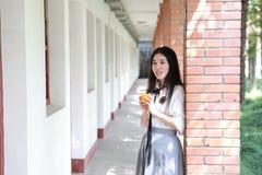 Il vestito grazioso cinese asiatico felice dello studente di usura della ragazza a scuola fa una pausa una parete porta una frutt Immagine Stock Libera da Diritti