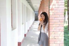 Il vestito grazioso cinese asiatico felice dello studente di usura della ragazza a scuola fa una pausa una parete porta una frutt Immagini Stock