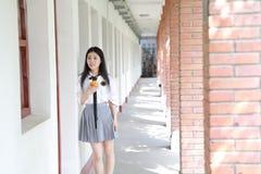 Il vestito grazioso cinese asiatico felice dello studente di usura della ragazza a scuola fa una pausa una parete porta una frutt Immagini Stock Libere da Diritti
