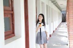 Il vestito grazioso cinese asiatico felice dello studente di usura della ragazza a scuola fa una pausa una parete porta una frutt Fotografia Stock Libera da Diritti
