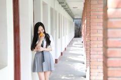 Il vestito grazioso cinese asiatico felice dello studente di usura della ragazza a scuola fa una pausa una parete porta una frutt Fotografie Stock