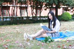 Il vestito grazioso cinese asiatico felice dello studente di usura della ragazza a scuola ha letto il libro si siede su erba Fotografia Stock