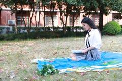 Il vestito grazioso cinese asiatico felice dello studente di usura della ragazza a scuola ha letto il libro si siede su erba Fotografie Stock Libere da Diritti