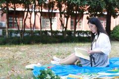 Il vestito grazioso cinese asiatico felice dello studente di usura della ragazza a scuola ha letto il libro si siede su erba Immagini Stock Libere da Diritti