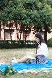 Il vestito grazioso cinese asiatico felice dello studente di usura della ragazza a scuola ha letto il libro si siede su erba Immagine Stock