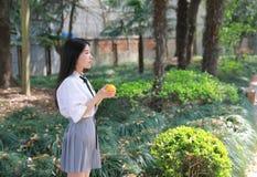 Il vestito grazioso cinese asiatico felice dello studente di usura della ragazza a scuola porta l'arancia della frutta in natura  Immagine Stock