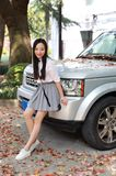 Il vestito grazioso cinese asiatico sveglio dello studente di usura della ragazza a scuola fa una pausa un'automobile Immagine Stock