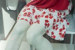 Il vestito rosso sulle gambe del manichino vende al dettaglio nel deposito di modo Fotografie Stock