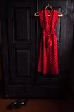 Il vestito rosso in un bianco punteggia su un gancio di legno Fotografia Stock