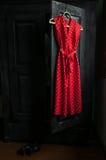 Il vestito rosso in un bianco punteggia su un gancio di legno Immagini Stock Libere da Diritti