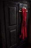 Il vestito rosso in un bianco punteggia su un gancio di legno su un guardaroba d'annata nero Fotografia Stock Libera da Diritti