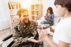 Il veterano in una sedia a rotelle ha ritornato dall'esercito Un uomo in uniforme in una sedia a rotelle con la sua famiglia immagini stock