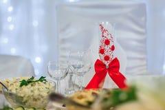 Il vetro è decorato con il nastro rosso per la tavola festiva di nozze Immagine Stock