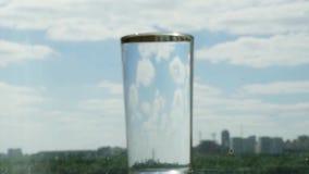 Il vetro con acqua sul fondo vago della città e del cielo blu cambia il fuoco 1920x1080 stock footage