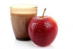 Il vetro con latte e la mela ha isolato Immagini Stock