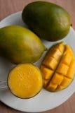 Il vetro del frullato fresco del mango con i manghi maturi Fotografie Stock