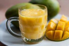 Il vetro del frullato fresco del mango con i manghi maturi Fotografia Stock