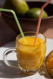 Il vetro del frullato fresco del mango con le paglie Fotografie Stock Libere da Diritti