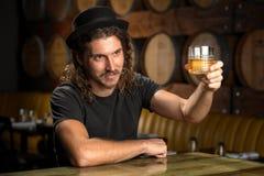 Il vetro del whiskey incoraggia il bourbon bevente dell'uomo alla moda ad una barra del ristorante della distilleria del whiskey Fotografie Stock