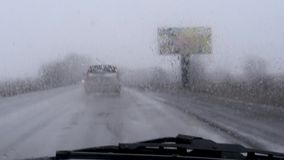 Il vetro dell'automobile è pulito dai tergicristalli in tempo piovoso, nevischio e pioggia video d archivio