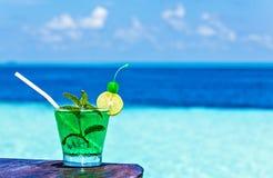 Il vetro della bevanda è su una tavola della spiaggia Fotografie Stock Libere da Diritti