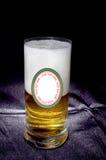 Il vetro della birra con l'etichetta sulla parte posteriore nera del fondo luminosa è Fotografie Stock Libere da Diritti