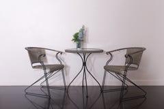 Il vetro della tavola rotonda e della sedia con il vaso di fiore, disposto su un fuoco scelto della tavola riflettente brillante, Fotografia Stock Libera da Diritti