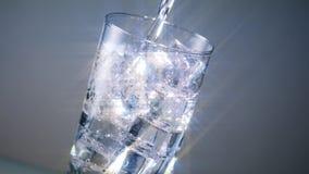 Il vetro di acqua ghiacciata versa il filtro dalla stella video d archivio
