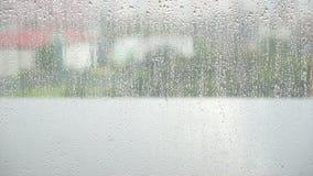 Il vetro di finestra bagnato, gocce di pioggia sul vetro di finestra sorge con il fondo vago nuvoloso della città video d archivio