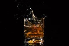 Il vetro di qualità di whiskey con spruzza dalla fetta di caduta di limone Fotografie Stock Libere da Diritti