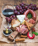Il vetro di vino rosso, il formaggio e la carne imbarcano, uva, fico, fragole, miele, grissini sulla tavola di legno rustica, bia Fotografie Stock Libere da Diritti