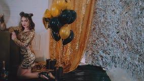 Il vetro tintinnante della donna allegra di champagne al partito sopra le stelle dorate di festa balloon il fondo Ragazza elegant stock footage