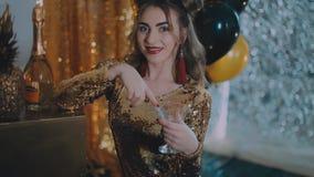 Il vetro tintinnante della donna allegra di champagne al partito sopra le stelle dorate di festa balloon il fondo Ragazza elegant video d archivio