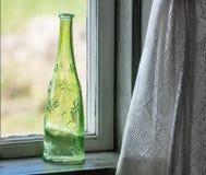 Il vetro verde ha decorato la bottiglia sulla finestra Fotografia Stock