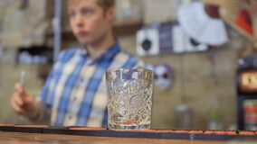 Il vetro vuoto su un contatore della barra, barista prepara il cocktail a fondo vago video d archivio