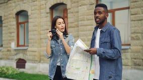 Il viaggiatore afroamericano bello dell'uomo sta esaminando la mappa quando il suo amico femminile attraente sta prendendo le fot stock footage