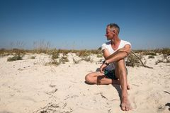 Il viaggiatore allegro dell'uomo si siede sulla spiaggia abbandonata Fotografia Stock Libera da Diritti