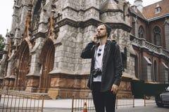 Il viaggiatore ambizioso e curioso sta stando sulla strada vicino alla vecchia costruzione di chiesa Immagine Stock