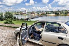 Il viaggiatore automatico studia una mappa sui precedenti della città Birsk Fotografia Stock